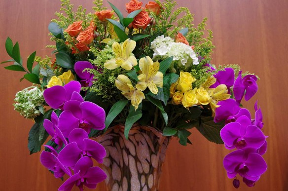 A vase of purple, white, yellow, and red flowers and greenery.