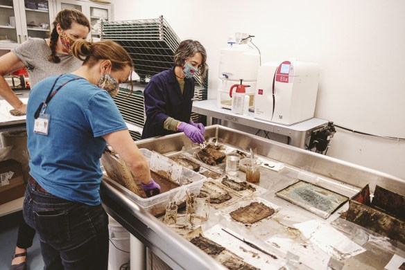 Photo shows 3 women, Conservator Sue Donovan, Curator Molly Schwartzburg, and Preservation Projects Specialist Nicole Royal, working with the contents of the time capsule, which are spread out over a work surface in a conservation lab environment.