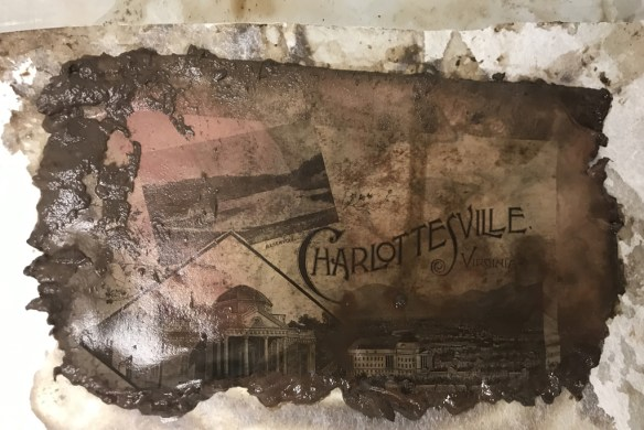 "Photo shows soggy, dirty and ragged paper sheet with images of Charlottesville. Word ""Charlottesville"" is clearly visible."