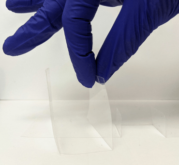 A gloved hand holds a U-shaped piece of Mylar, which will form 3 sides to a box for the football