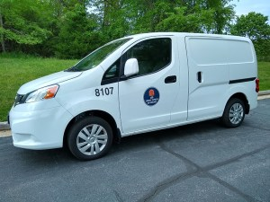 A white van with the UVA Library logo on the door, parked at the curb on a paved street.
