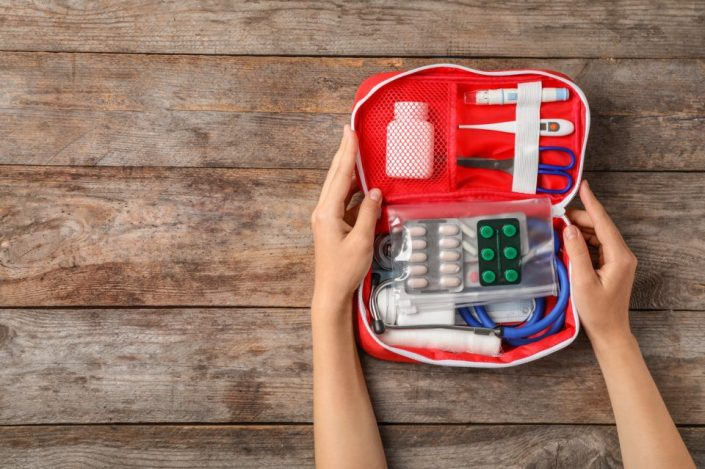Woman holding first aid kit on wooden background.