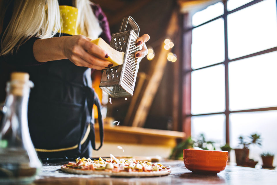 Woman hand grating cheese on a pizza