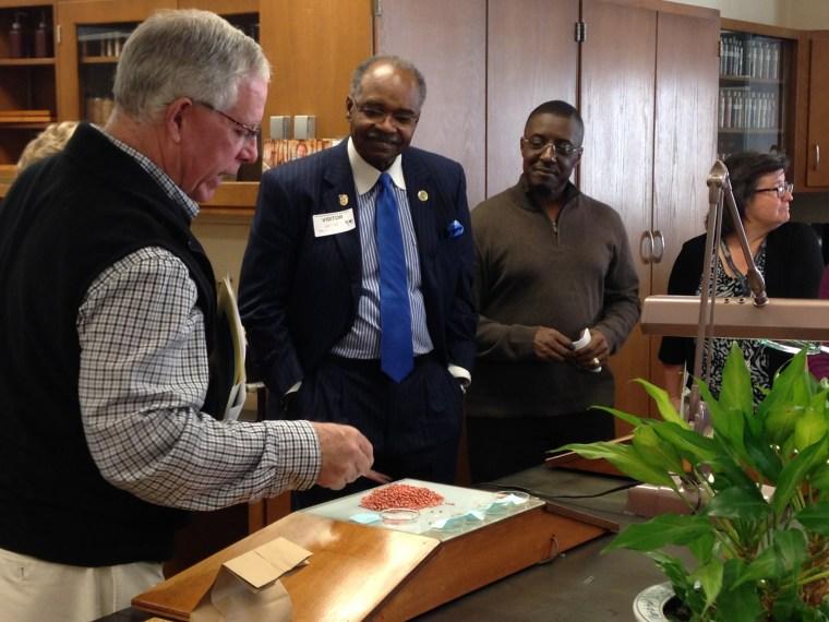 Turf & Seed Program Manager Dale Morris shows legislators the lab.