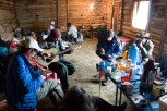 The group gathers on a rainy afternoon inside a rented dirt-floor cabin to hear the father-son duo of Aaron and David Putnam entertain with traditional American folk music. (Sarah Kramer/Medill)