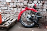 The back wheel of a motorbike is discarded after being removed to attach a finished Qingqi carriage. (Kat Lonsdorf/MEDILL)