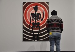 A man stands before a painting of a skeleton against a red target backdrop in the Art AIDs America exhibit.
