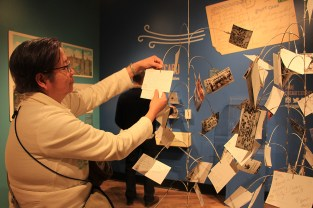 The event attracted attendees from several communities. Tess Tan, from Skokie, wrote a postcard at the museum for her niece who fell in love with Chicago when she first visited. (Wenjing Yang/MEDILL)