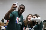 NBA Cares Ambassador Felipe Lopez taking a selfie with volunteers. (Athena Liu/MEDILL)
