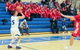 Conner Tomasic attempts a 3-point shot early in the game as the Munster basketball team watches from the bleachers behind the basket. The Mustangs arrived early enough to watch most of the game between Lake Central and Crown Point. (Erik Alcantar/MEDILL)