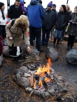 Pamala Silas throws tobacco from her tobacco tie into the bonfire. Silas is the associate director of community outreach and engagement at Northwestern University's Center for Native American and Indigenous Research. (Katie Rice/Medill)