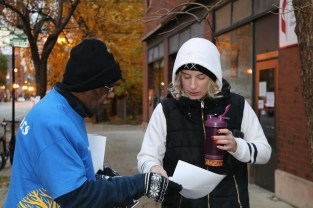 Reggie Griffin, a volunteer with the Jane Addams Senior Caucus, asks a voter to support the rent control referendum outside a polling place Nov. 6. (Becky Dernbach / MEDILL)