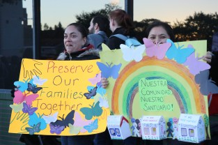 "Logan Square is known for its rich Hispanic history, but minority residents say they are targeted unfairly for evictions. The march reflected the neighborhood's demographics. The sign at the right reads,""our community, our sanctuary."" (Alexis Shanes/MEDILL)"
