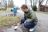 Gabriel Filippelli rinses off his scoop in a puddle outside Mikey Reid's house so as not to mix soil from different locations into one sample. (Becky Dernbach/MEDILL)