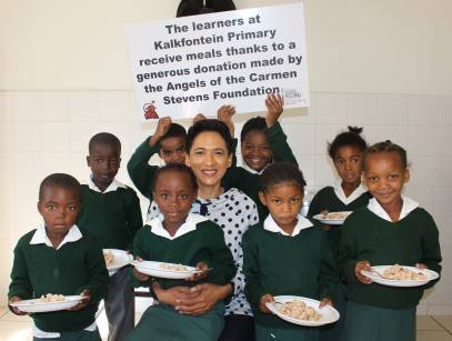 several school children from Kalkfontein Primary School Belhar sit with Carmen Stevens who helped raise money for their school lunch program