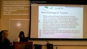 Conference presenter at podium discussing neurobiology of trauma
