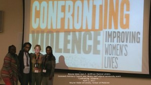 Conference attendees in front of screen saying Confronting Violence Improving Women's Lives
