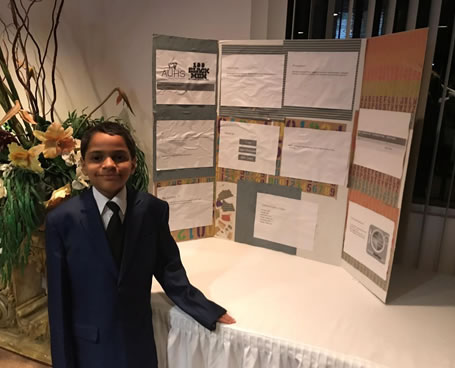 a young man standing in front of his tabletop presentation
