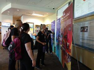 Students in scrubs read exhibit panel text