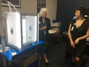 Two librarians stand next to a 3D printer in operation.