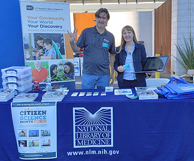 two librarians at an exhibit booth displaying some of the information materials