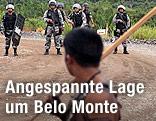 Indigener mit Holzstange vor brasilianischen Polizisten