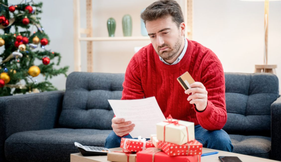 Man holding credit card looking at bill worries about debt. He is sitting in front of christmas tree.
