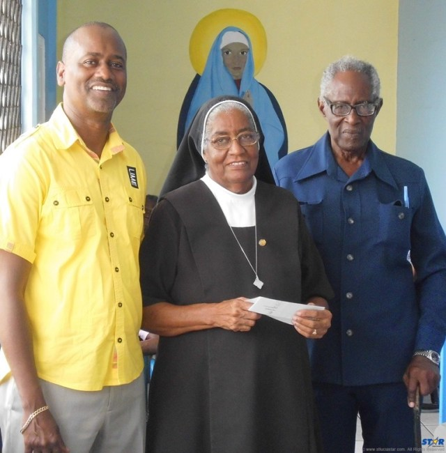LIME GM Chris Williams and Mr George Theophilus flank Sister Olivia Oculien of the Marian Home.
