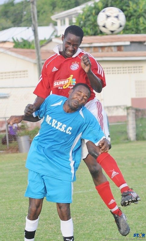 Gros Islet player (in red) heads the ball away from Mabouya Valley defender.