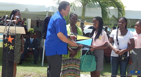 Prime Minister Kenny Anthony presents students and parents with the new laptop on Wednesday.