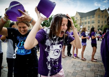 "Students Jenny Murtha (right) and Sarah Rae LaValla douse themselves with ice water as part of UST's mass ""Ice Bucket Challenge."""