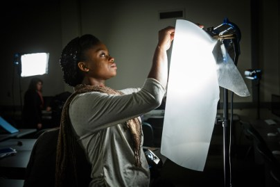 A student applies a diffuser to a light during a video production class .