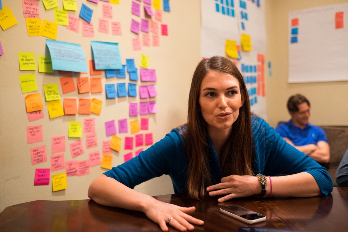 Kara Gamelin in front of sticky notes the students used to work through their empathy exercises.