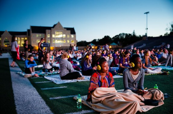 Students watch a movie on the O'Shaughnessy Stadium video screen.