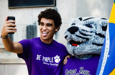 Brazilian international student Gustavo Faria takes a selfie with Tommie before the March Through the Arches.