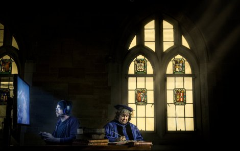 Theology professor Corrine Carvalho (right) and student Mike Best pose for a photo shoot near a stained glass window in O'Shaughnessy-Frey Library. Carvalho and Best have done extensive work on the intersection of the Old Testament and Video Games. Taken for St. Thomas magazine.