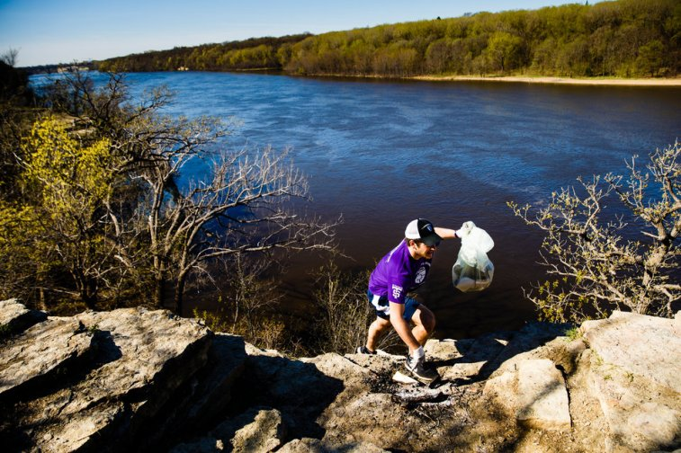 Students pick up trash along the shore of the Mississippi River in St. Paul during a St. Thomas Day of Service April 22, 2017.