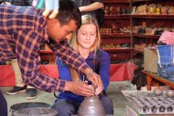 "Third place, Global Classroom: Bryjett Nordmark, Bhaktapur, Nepal. ""The Potter and The Clay: A local potter helps me form a clay cup in Potter's Square. He is helping shape the clay into a work of art and helping shape the mind to open up to new ways of thinking during an experience one can only have by studying abroad."""