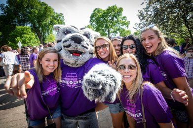 Seniors pose for a group photo with Tommie during the 2018 March Through the Arches ceremony for graduating seniors on May 18, 2018 in St. Paul.