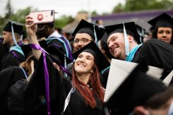 Students take a selfie during the 2018 Graduate Commencement ceremony in O'Shaughnessy Stadium on May 18, 2018 in St. Paul.