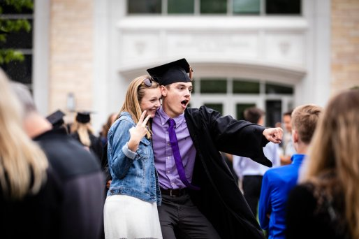 A graduating senior poses for a photo with a friend during the 2018 Undergraduate Commencement ceremony in O'Shaughnessy Stadium on May 18, 2018 in St. Paul.