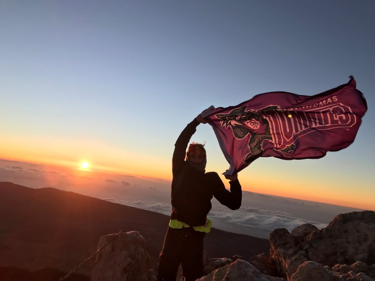 This photo was taken at the top of Mount Teide, a 12,000-foot volcano in Tenerife, Spain. Behind me is the sunrise over the clouds. The hike started at 11:00 PM and we reached the top just as the sun began to rise at 7:30 AM. I couldn't help but show my Tommie pride in this setting! After appreciating the beauty from on top of the mountain, I hiked back down and finished around 1:30 PM. This was one of my favorite hikes I have ever completed.