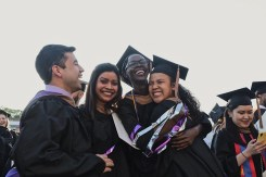 Students hug at the graduate commencement ceremony.