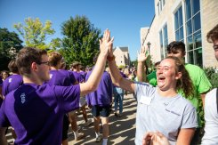 A student gets a high five during the annual March through the Arches to celebrate the start of the school year and the arrival of a new class of freshmen on campus on September 3, 2019, in St. Paul.