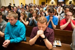 Students fold their hands in prayer during the Opening Mass Sept. 5, 2019 in the newly renovated interior of the Chapel of St. Thomas Aquinas.