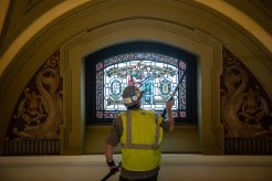 A worker cleans a stained glass window in the Chapel of St. Thomas Aquinas during renovations on July 18, 2019, in St. Paul.