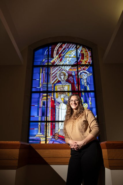 Art History and Catholic Studies major Hannah Rose Shogren Smith poses for a portrait in the O'Shaughnessy-Frey Library in front of the St. Thomas Aquinas window. Mark Brown/University of St. Thomas