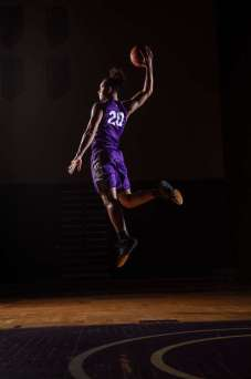 Elijah Hannah leaps during a photoshoot for the UST Men's Basketball schedule poster. Mark Brown/University of St. Thomas