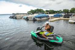 Schulze Innovation Scholar Dylan Dierking founded Foodski, a jet ski food delivery business based in White Bear Lake. Dierking takes orders for deliveries from customers ordering food from area restaurants and delivers them to homes and boats around the lake on his jet ski. Photos taken on July 22, 2020, in White Bear Lake. Dylan Dierking takes a delivery to a dock in a marina for delivery via jet ski.