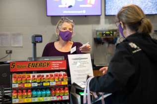 Catering Services Director Molly Boyne serves a customer from behind a clear protective barrier in Summit Marketplace in the Anderson Student Center. Mark Brown/University of St. Thomas